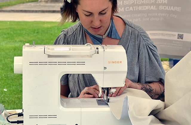 The artist sews the white fabric together.