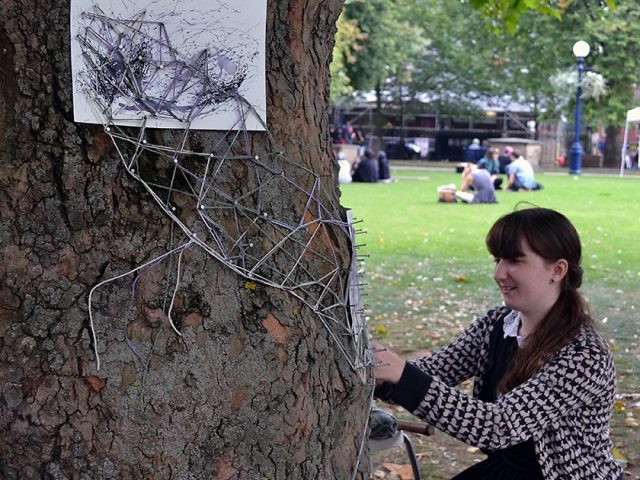 The artist hammers nails around the tree and stretches wool around the nails to create forms.