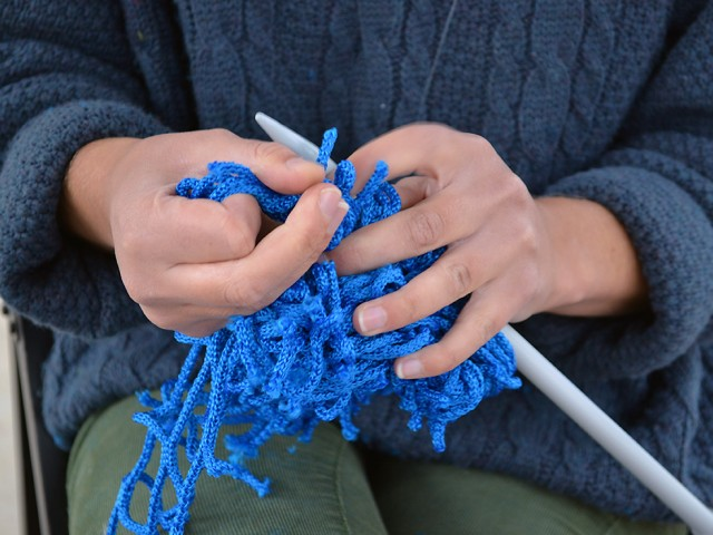 A woman is knitting with blue wool and big needles.