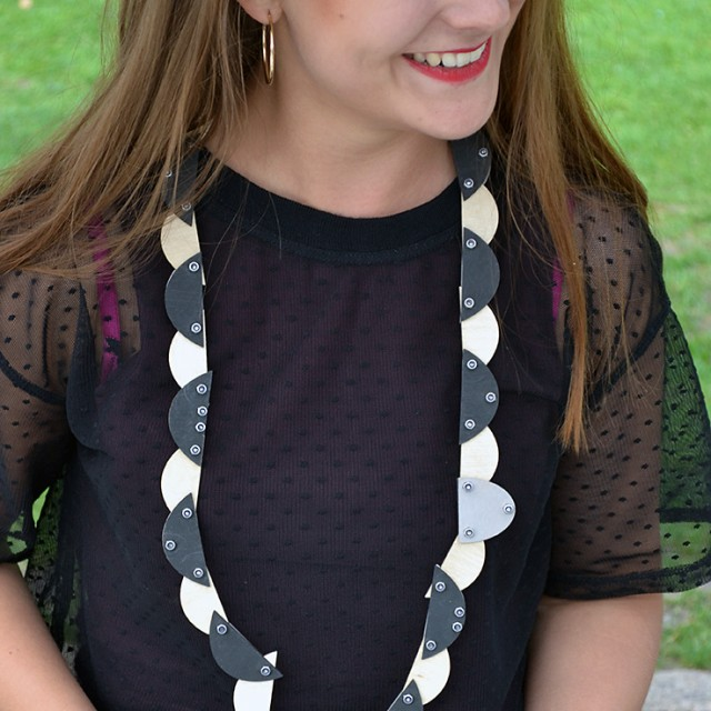A girl is very proud of her self-made necklace with black and white semicircular discs.