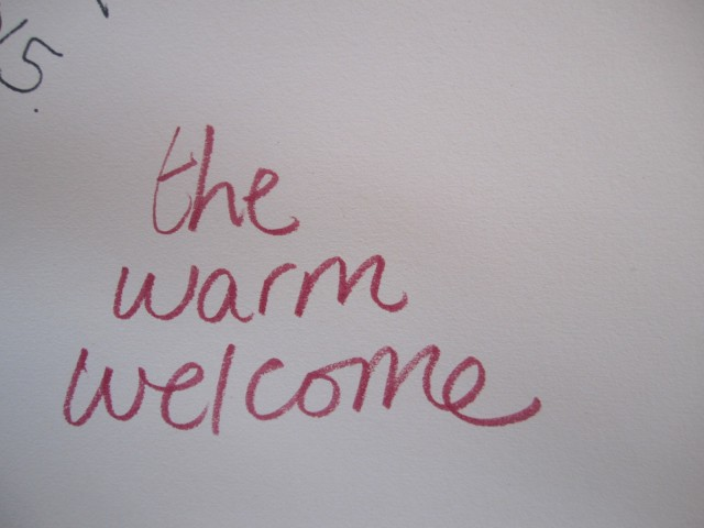 "on a white sheet of paper someone wrote ""the warm welcome"" with a red pen"