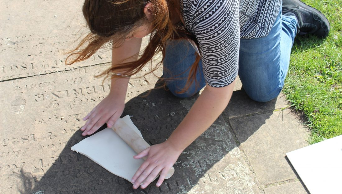 an artist rolls a slab of clay over a gravestone set in the path.