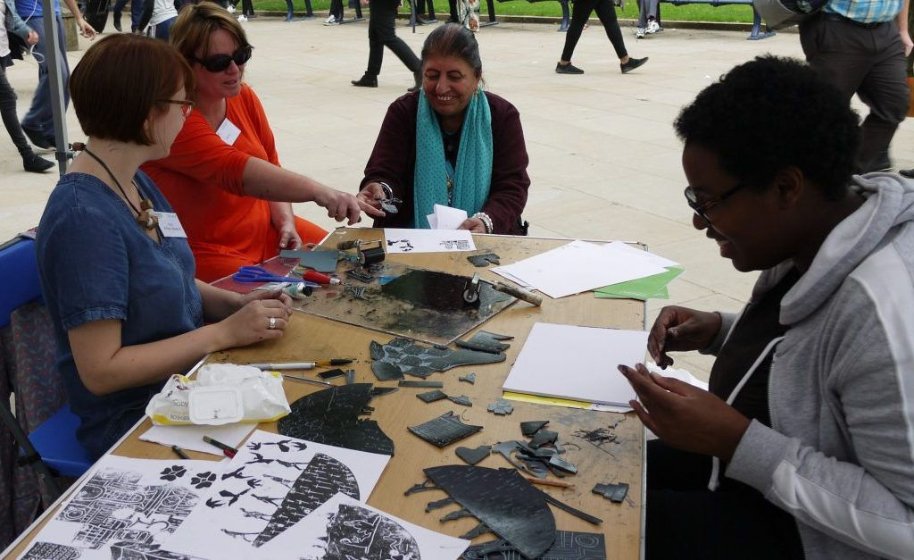 Three women interact and talk to the artist around a table whilst linoprinting.