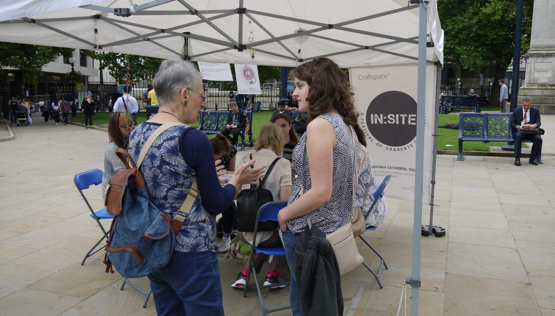 An older woman is talking to the artist about her work at In:Site.