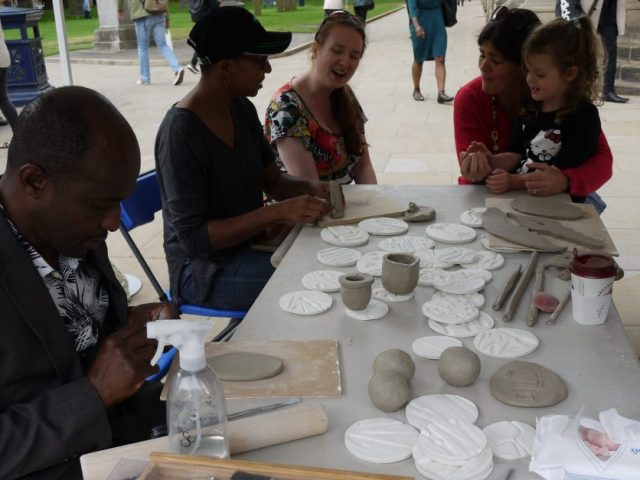 Members of the public gather around a table and play with clay.