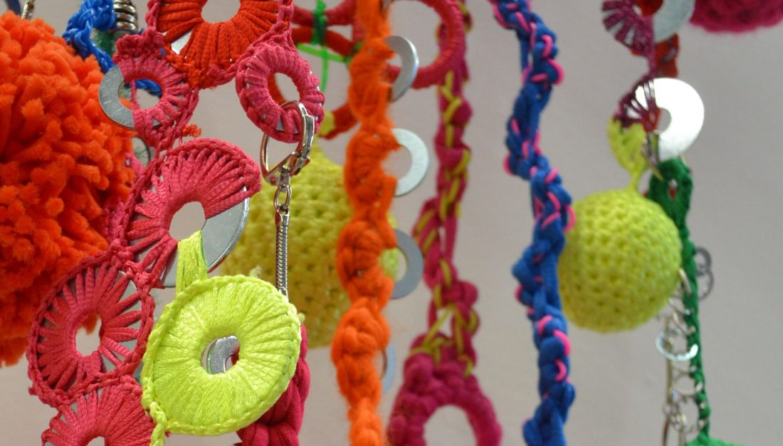 A hanging installation of colourful threads and yarns with metal washers, keyring and jumprings attached.