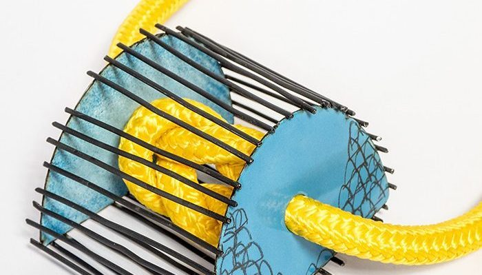 Jewellery incorporating metal, yellow rope and blue enamel.