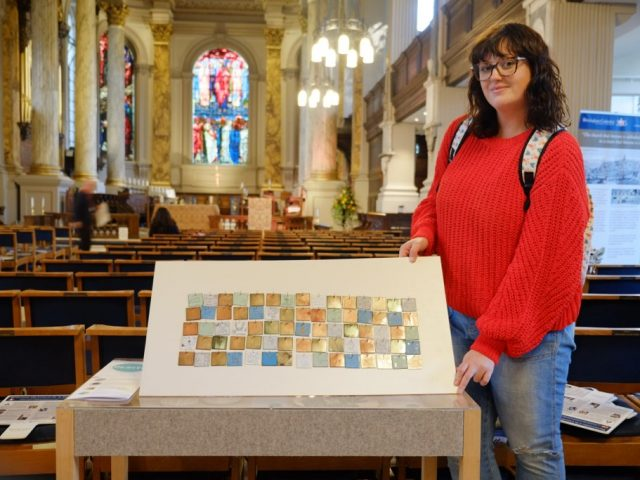 The artist shows proudly the tiled collection of drawings