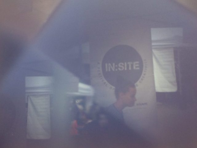 The In:Site sign on a banner with a lady walking past as seen through a camera obscura.