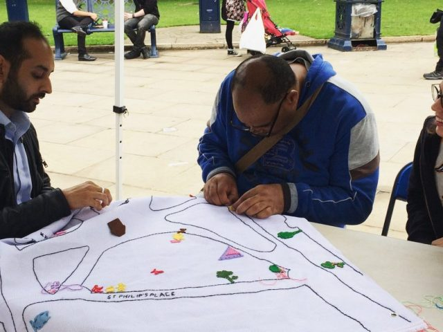 People are sewing something on the map of Cathedral Square.