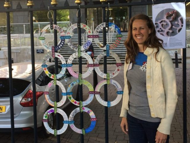 The smiling artist stands next to painted circles attached to the fence.