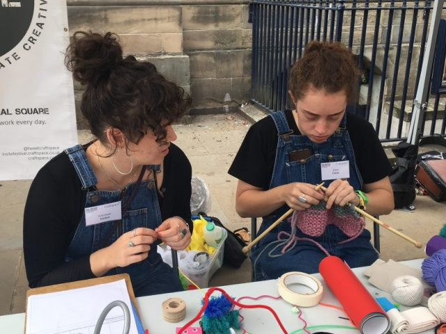 artist is knitting with a volunteer