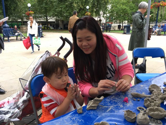 A mother is sculpting the clay with her son.