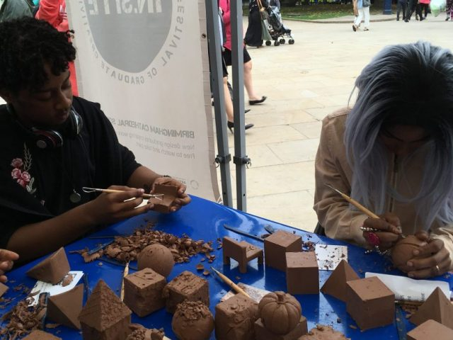 two people carving into clay