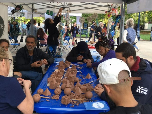groups of people sitting around table carving into clay