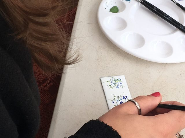 A woman is painting flowers on an enamel tile.