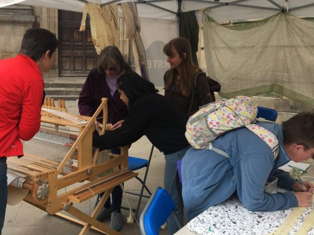 The artist is watching two participants at the weaving loom.