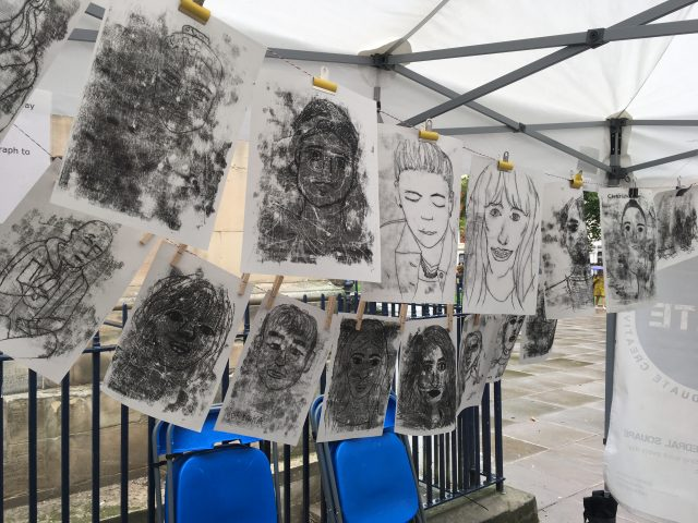 There were so many drawn portraits of the passersby that they hung them on a second line.