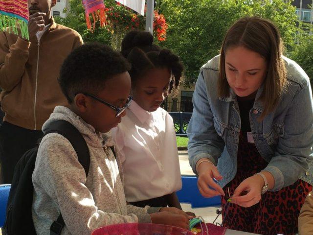 The artist is helping children stitching