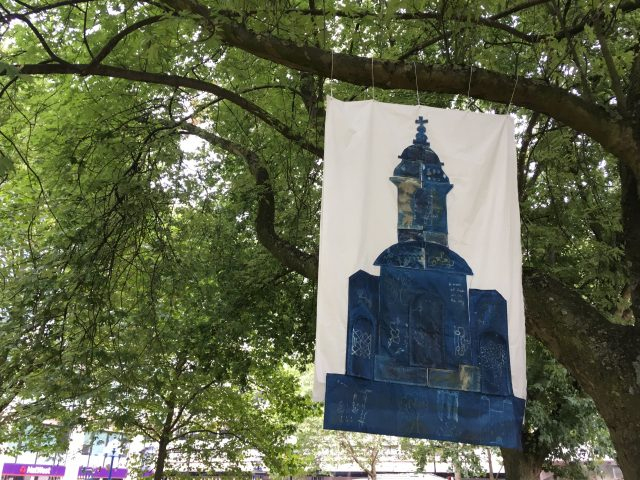 The fabric piece of the church was hung in the trees for passersby to view.