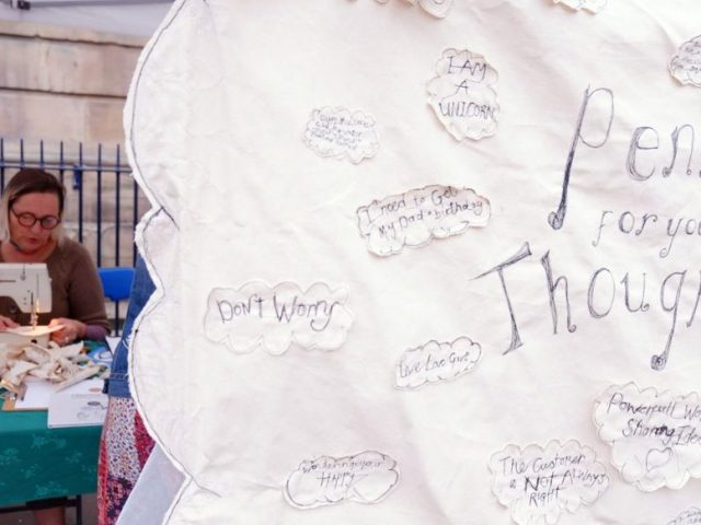 Front of image stitched words and phrases, artist on sewing machine in the background