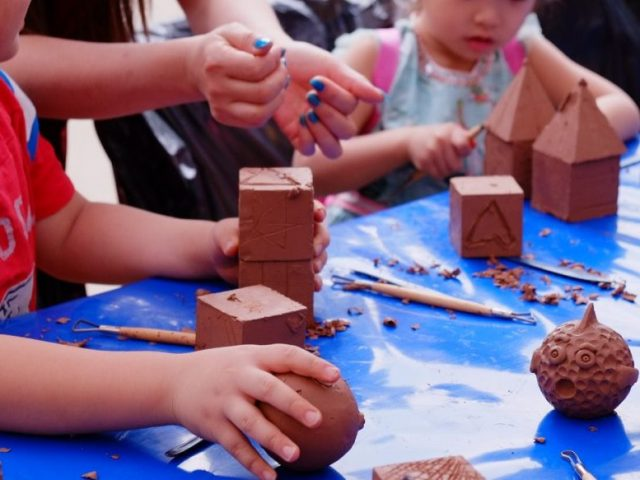 close up of childrens hands playing with and carving clay