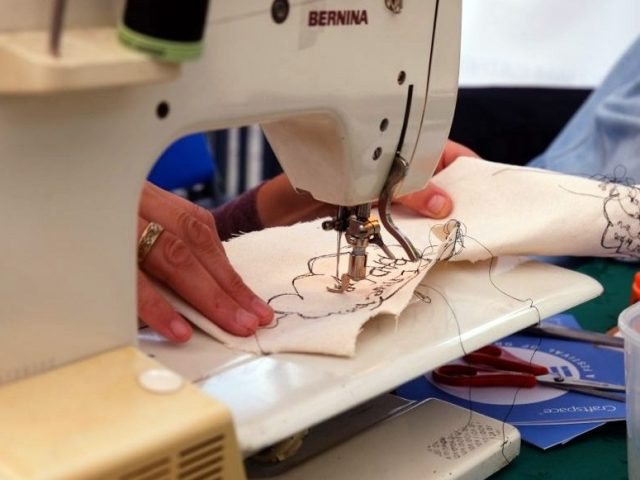 The artist on the sewing machine.