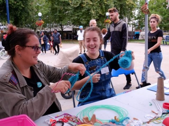 The artist and a woman are having fun playing with wool.