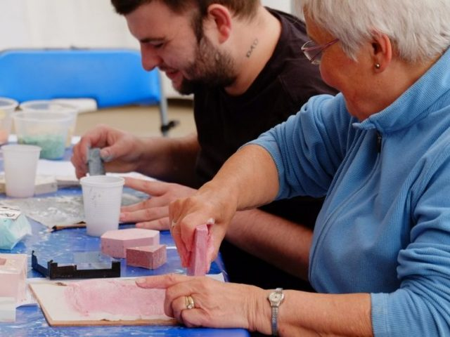 two people sand down jesmonite plaster cases in order to see the finished result