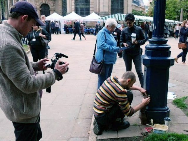 film maker filming artist Marek making clay sculptures on a lamp post