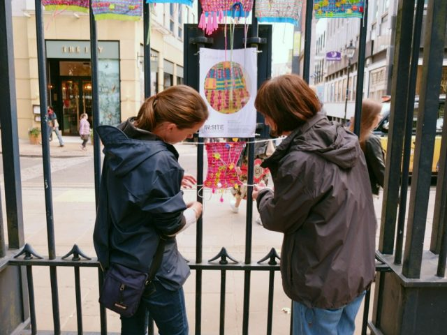 Two women are hanging up their colourful textile piece.