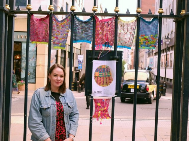 The happy artist is standing next to the colourful textile pieces which are hung up on a fence.