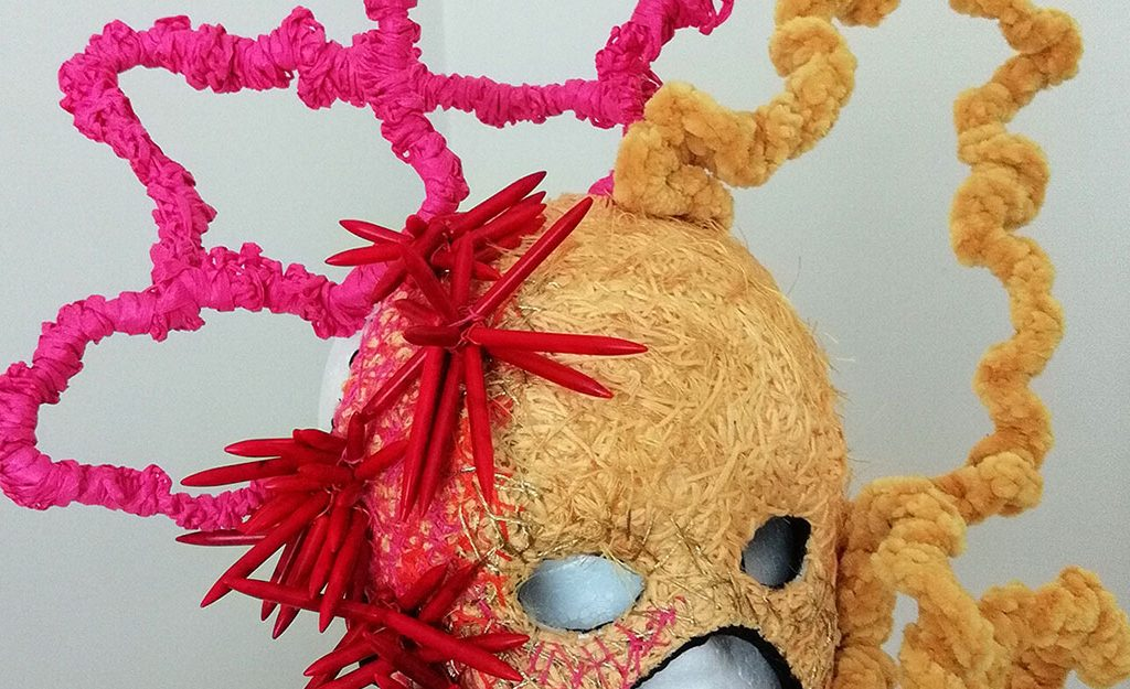sculptural face mask in pink and yellow fabric