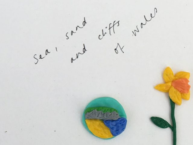 'sea, sand and cliffs of wales' with small beach scene and a daffodil made from modelling clay