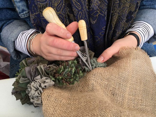 artist hands using rag rug tool