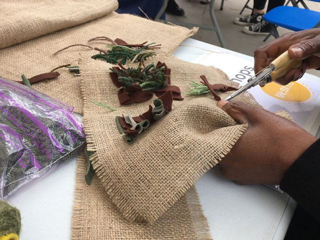 hands using tool to rag rug