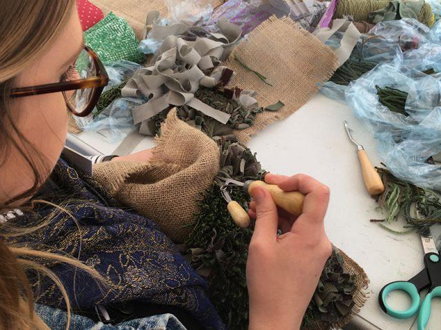 artist using tools to rag rug
