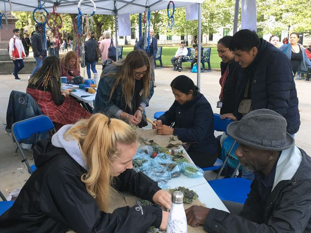 people learning how to rag rug from artist and volunteer