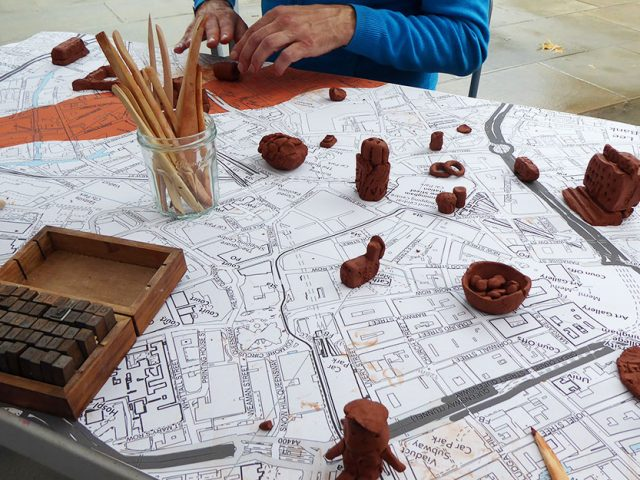 clay objects and tools on a table with Birmingham map