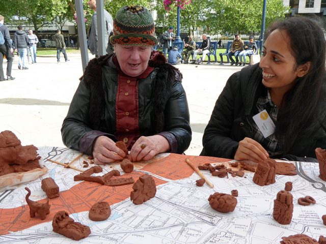 volunteer and participant making clay sculptures