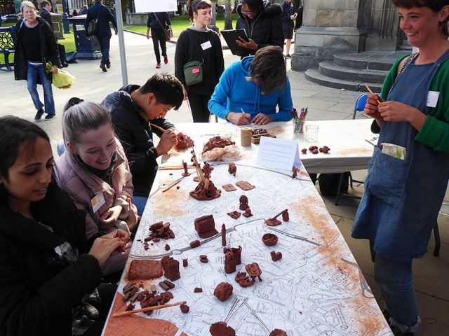 table with people making small clay sculptures