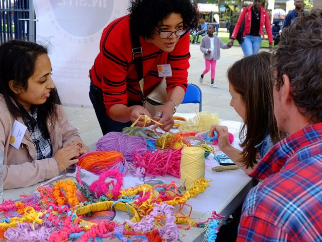 artist and volunteer showing participant different colourful yarns