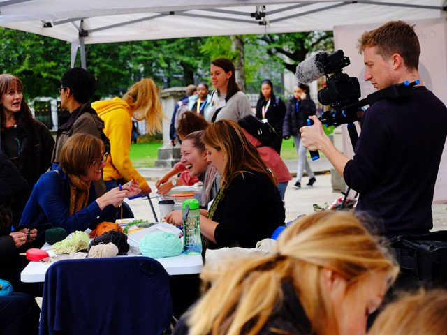 film maker filming table of artist and public