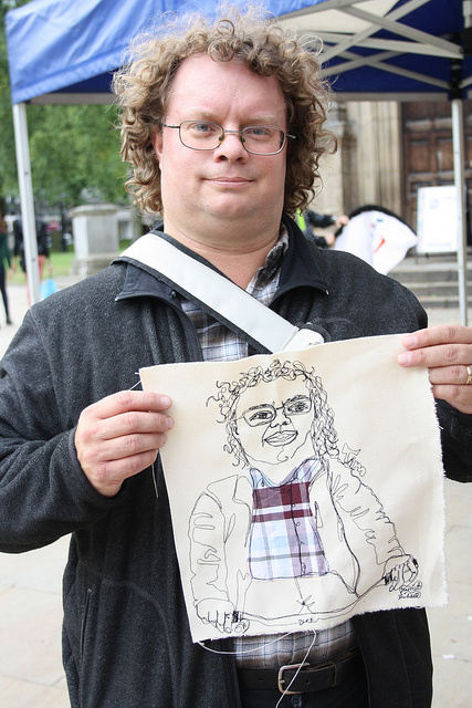 A man holds up a cloth the artist has sewn him onto.