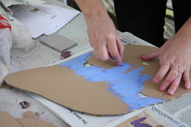 The person paints the cardboard blue.