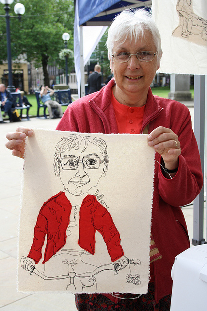 An elderly lady is holding up a fabric on which the artist has sewn her.