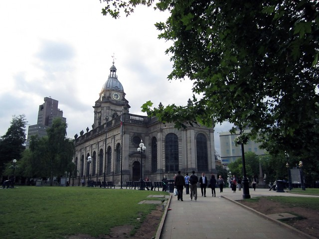 A large stone cathedral surrounded by wide paths and lawns.