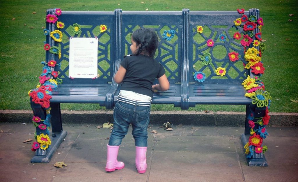 a young girl stands by a park bench which has been decirated with bright crocheted flowers.