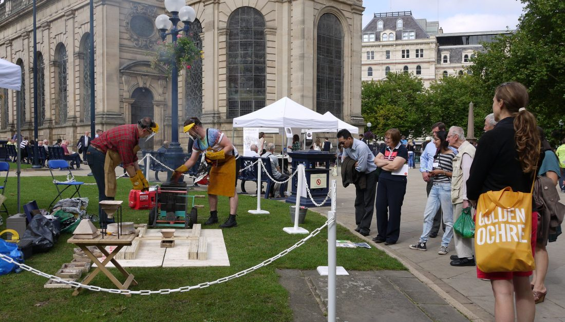 Two men using a machine in the grounds of St Phillip's Cathedral to pour liquid pewter into a mould.