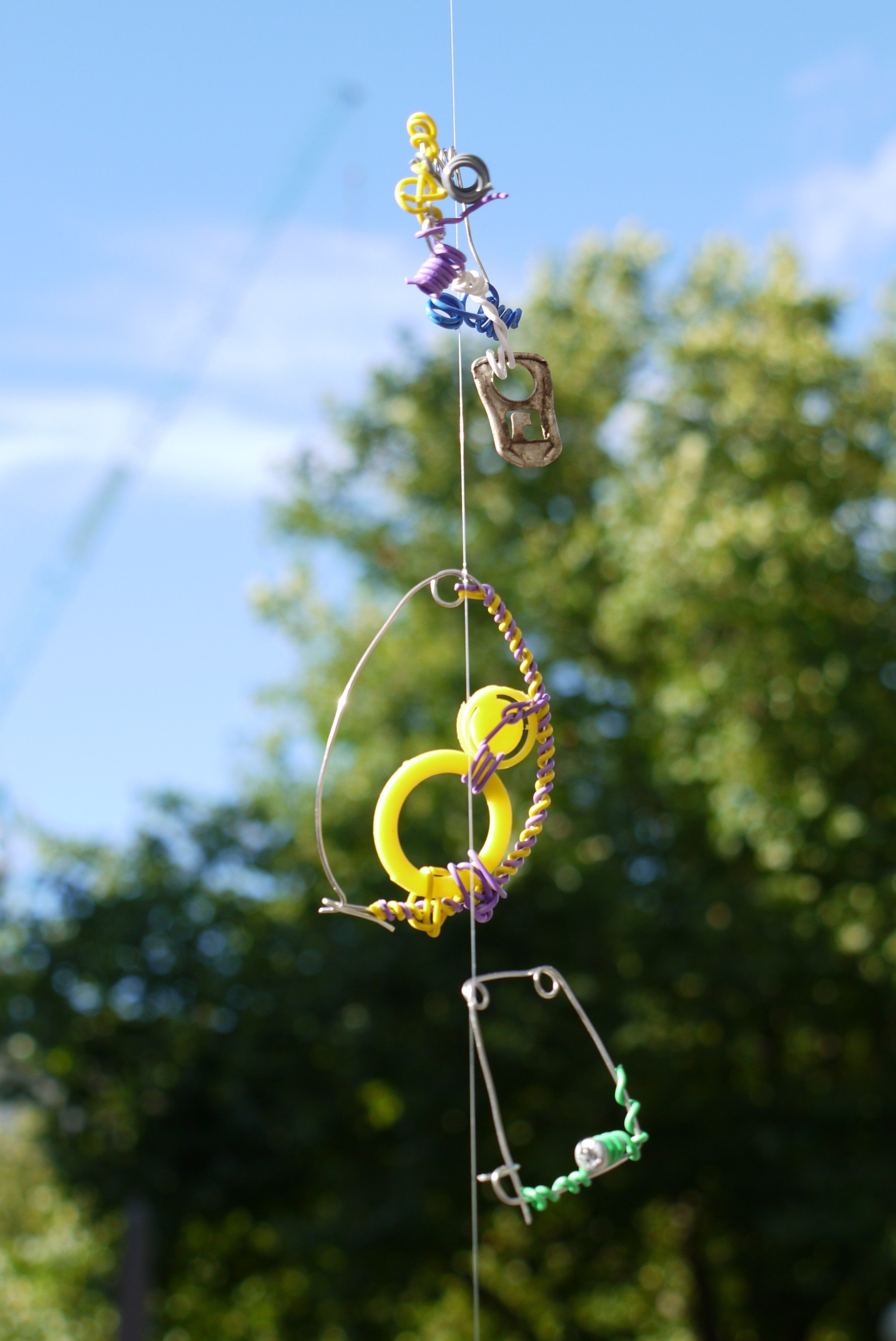 made from found objects such as rusted metals and twigs, with silver and colourful covered metal wire